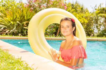 Beautiful girl with swim ring in swimming pool