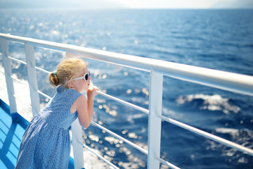 Adorable young girl enjoying ferry ride staring at the deep blue sea. Child having fun on summer family vacation in Greece. Fototapete