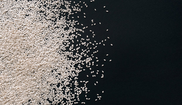 Scattered white sesame seeds on black textured paper background. Close up, copy space, top view. Calcium concept.