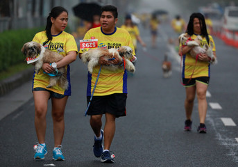 Pet owners carry their dogs as rain pours during a fun run for charity in Pasay City