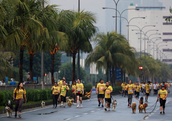 Pet owners walk with their dogs during a fun run for charity in Pasay City