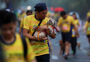 A pet owner carries his dog as it rains during a fun run in Pasay City