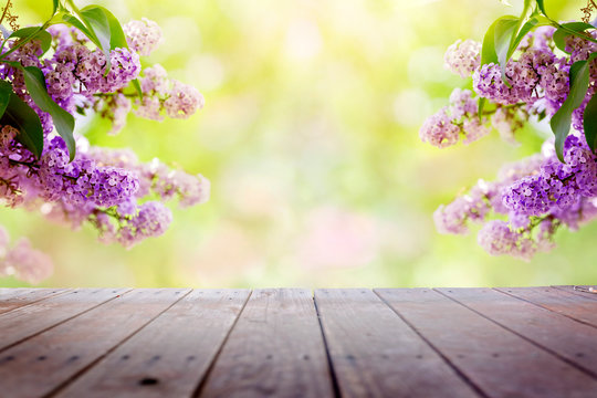 Lilac flowers in the garden over wooden deck background