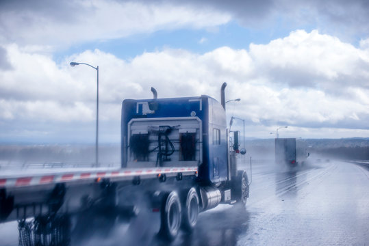 Big rig blue classic semi truck with flat bed semi trailer moving on the wet raining road behind another semi truck with rain dust fog