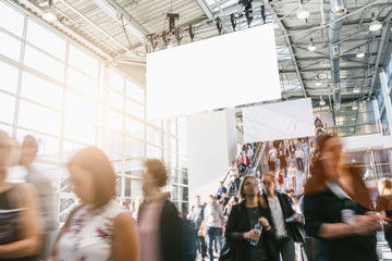 Wall Mural - crowd of blurred business people at a trade show, with copy space banner