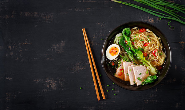 Miso Ramen Asian noodles with egg, pork and pak choi cabbage in bowl on dark background. Japanese cuisine. Top view. Flat lay