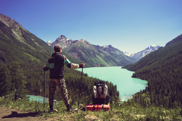 Photo from back of tourist man with walking sticks with his hands up on mountain hill near lake. tourist holding sticks for Nordic walking.