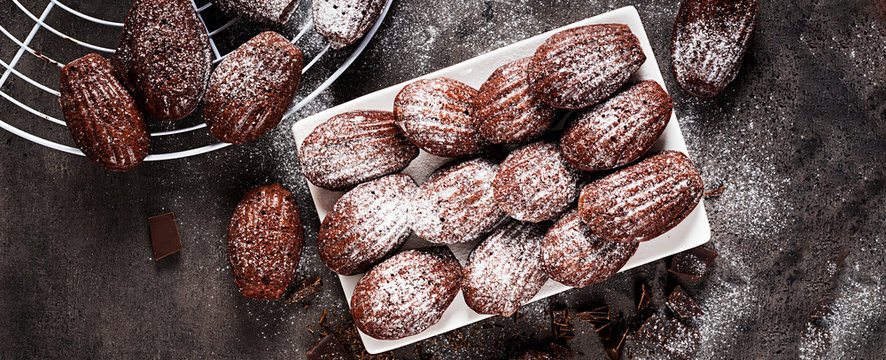 Chocolate cookies. Homemade Chocolate Madeleines on dark table. French cuisine. Banner. Top view