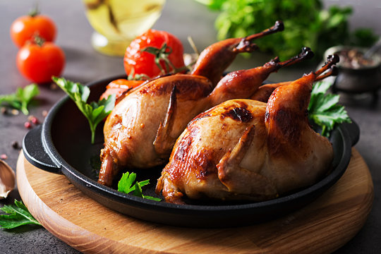 Baked quails in pan on a dark background