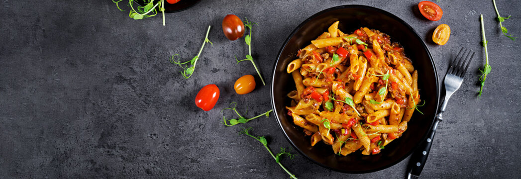 Penne pasta in tomato sauce with meat, tomatoes decorated with pea sprouts on a dark table. Top view. Banner