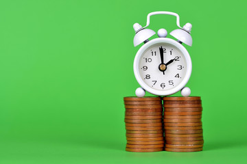 Pile of coins and white alarm clock on green background. Time to save money concept.