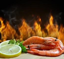 Fresh shrimp with slice of lemon on table.