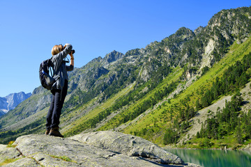 Photographer taking picture photos with DSLR camera at Gaube lake. Hautes Pyrenees, France.