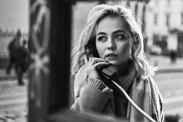 Young beautiful blond woman making an important call in a vintage public phone booth on a sunny evening