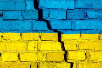 Flag of Ukraine on the brick wall with big crack in the middle. Destruction and separatism concept