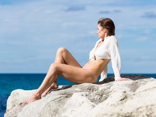 Female person resting on wild rocky seashore