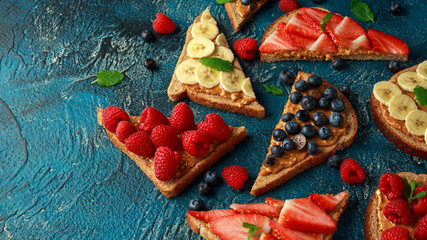 Peanut butter sandwiches with fresh strawberry, blueberry, raspberry and banana whole meal toasts.