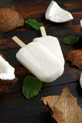 Homemade coconut popsicles, ice lolly, on wooden table. Summer food.