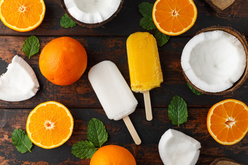 Homemade Coconut, Orange popsicles, ice lolly, on wooden table. Summer food.