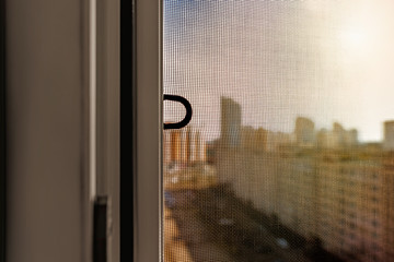 Open window with a mosquito screen to prevent insects and bugs, like flies, bees, mosquitoes or wasps from entering