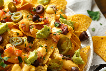 Mexican nachos tortilla chips with olives, jalapeno, guacamole, tomatoes salsa and cheese dip. close up
