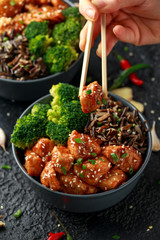 Teriyaki chicken, steamed broccoli and wild rice served in two Asian clay bowls.