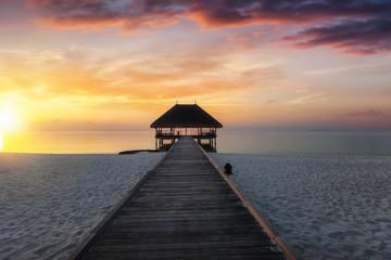 Sonnenuntergang auf den Malediven mit Holzsteg und Wasser Villa im Abendrot