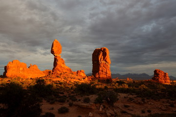 Balanced Rock in Arches National Park with sun setting and cloudy sky, Utah
