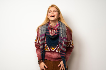 Hippie woman over white wall smiling a lot while putting hands on chest