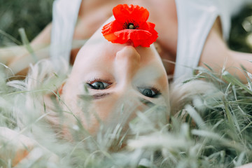 blonde girl with poppy flower in her mouth is laying on the grass