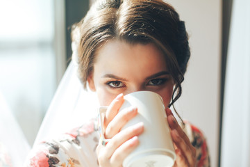 A beautiful young bride is enjoying her morning coffee in a hotel room near a large window. Bride's morning