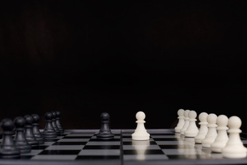 Picture of chess pawns on the chessboard. isolated on the black background.