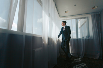 A young handsome man is preparing for his wedding. Portrait of the groom near a large window in the hotel room. Morning groom