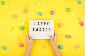 Easter composition, greeting card with child hand, lightbox text Happy Easter, colored decorative eggs on color background.