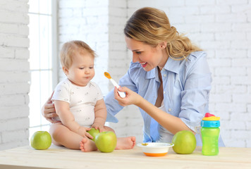 A young mother in the kitchen feeds vegetable puree with a spoon of her 9-month-old child