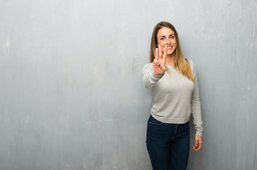 Young woman on textured wall happy and counting three with fingers Wall mural