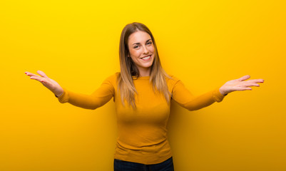 Young woman on yellow background presenting and inviting to come with hand