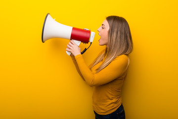 Young woman on yellow background shouting through a megaphone to announce something in lateral position
