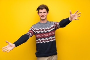 Teenager man over yellow wall presenting and inviting to come with hand