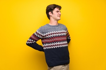 Teenager man over yellow wall suffering from backache for having made an effort