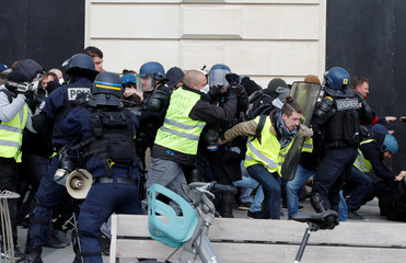 """Protesters wearing yellow vests clash with French riot police during a demonstration by the """"yellow vests"""" movement in Paris"""