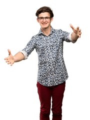 Teenager man with flower shirt and glasses presenting and inviting to come with hand over isolated white background