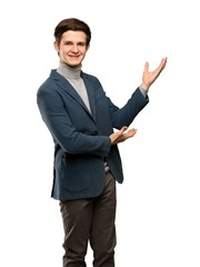 Teenager man with turtleneck extending hands to the side for inviting to come over isolated white background