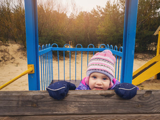 playful happy little girl at playground on sunny spring day