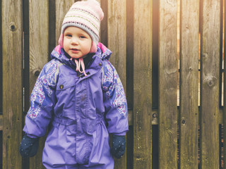 little girl wearing purple coverall standing by the wooden fence