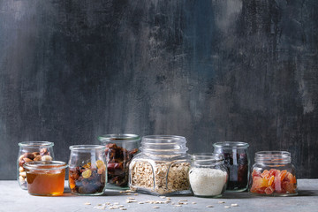 Variety of dried fruits, nuts, honey and oat flakes in different glass jars for cooking homemade healthy breakfast muesli or granola energy bars on grey blue table.