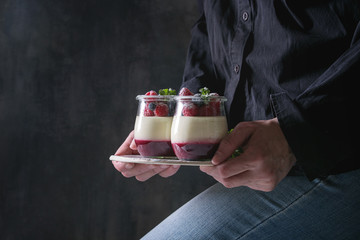 Woman in black shirt holding in hands homemade classic dessert Panna cotta with raspberry and blueberry berries and jelly in jars, decorated by mint and sugar powder. Dark background.