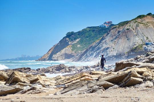 Surfer walks on rocky beach with surfboard. Atlantic ocean coast. Bidart, France