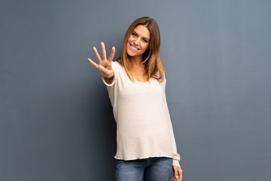 Blonde woman over grey background happy and counting four with fingers
