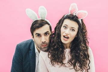 Young lovers couple on the pink background. With a bunny ears on the head. Having put his head on his wife's shoulder, the spouses made a surprised facial expression, opening their mouths. Easter.
